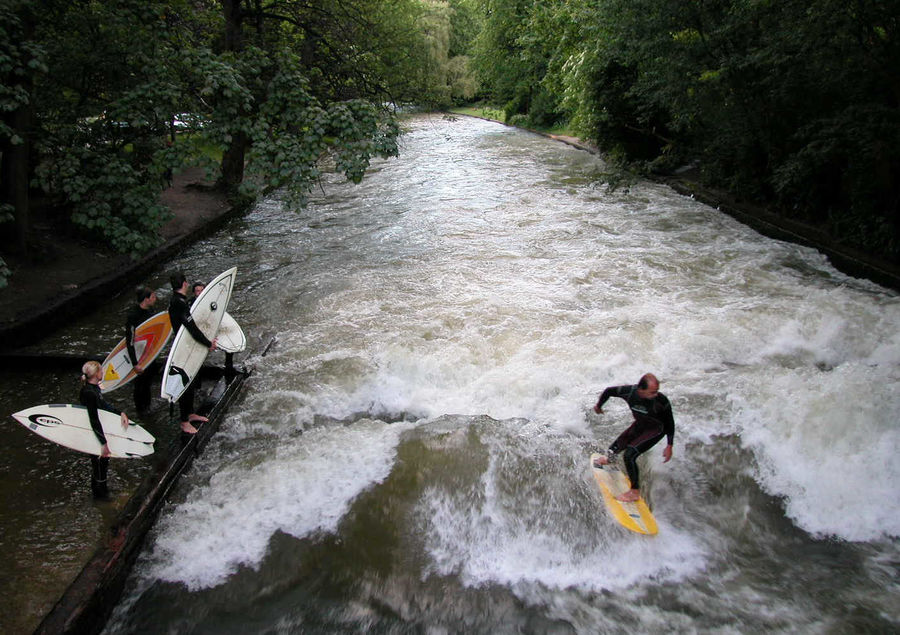 Surfers on the Eisbach branch of the Isar River, as seen from the Eisbach Bridge, Englisher Garten, Munich, Germany