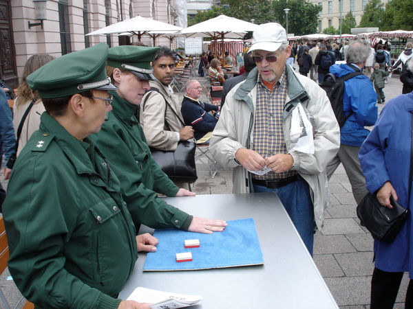 Police demonstrating a shell-game swindle near Checkpoint Charlie, Berlin, Germany