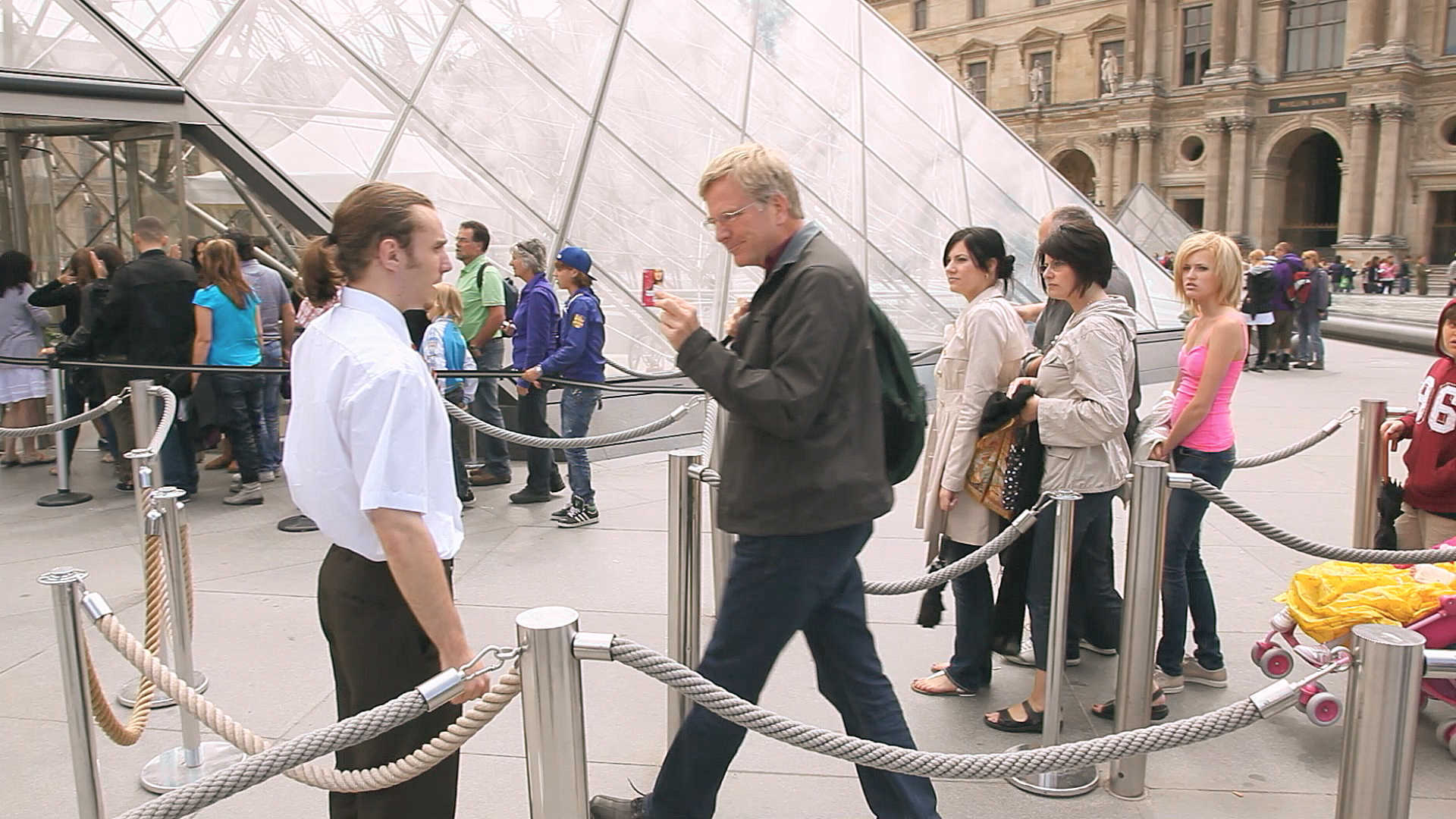 Rick Steves passes the museum line at the Louvre