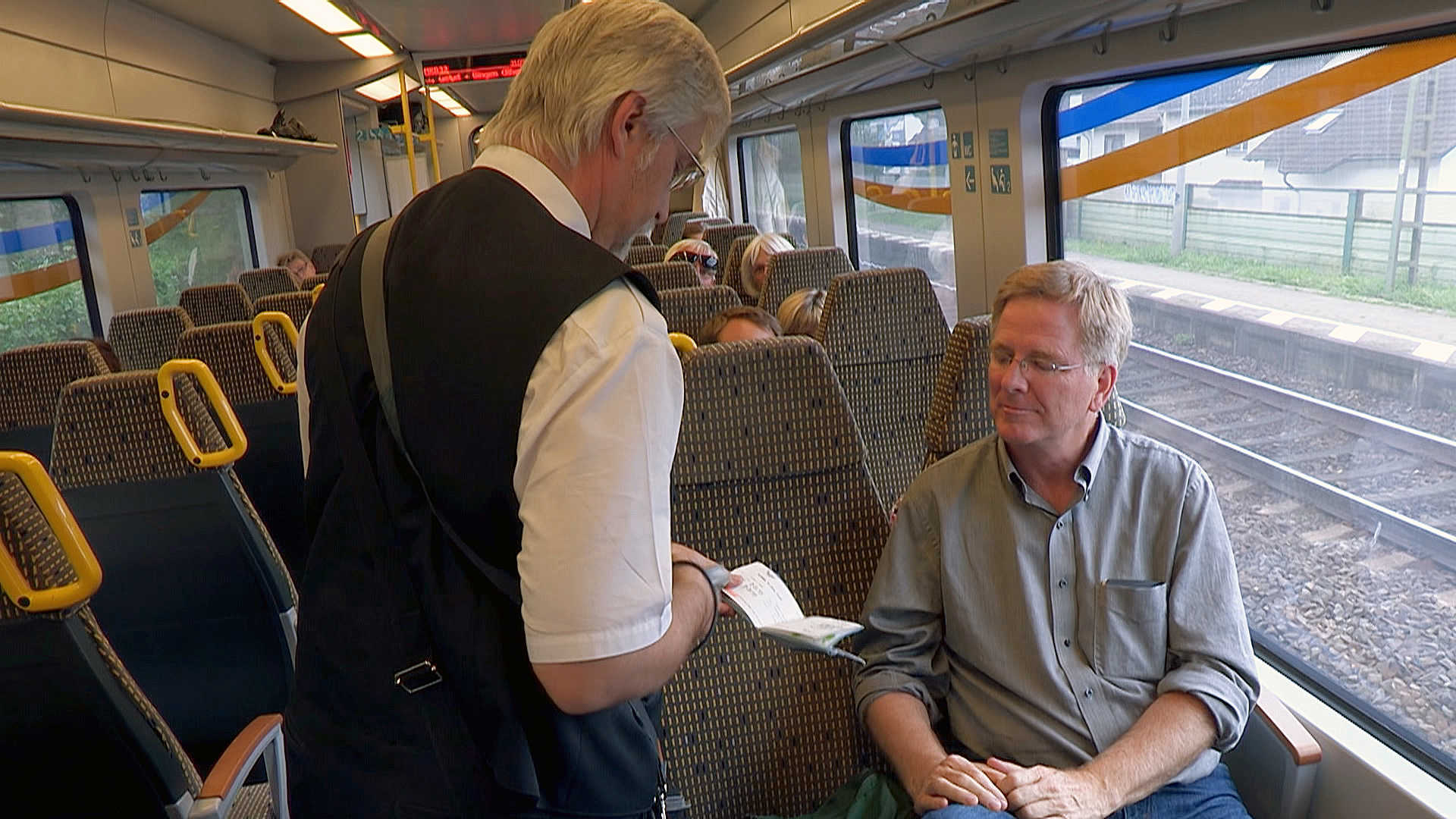 Rick Steves has his ticket examined by the train conductor