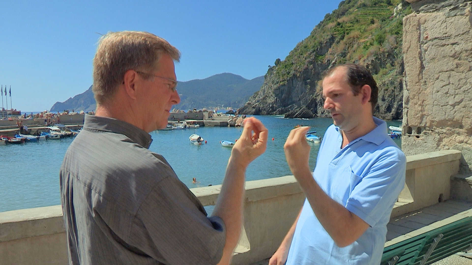 Rick Steves gesticulates with an Italian in Vernazza