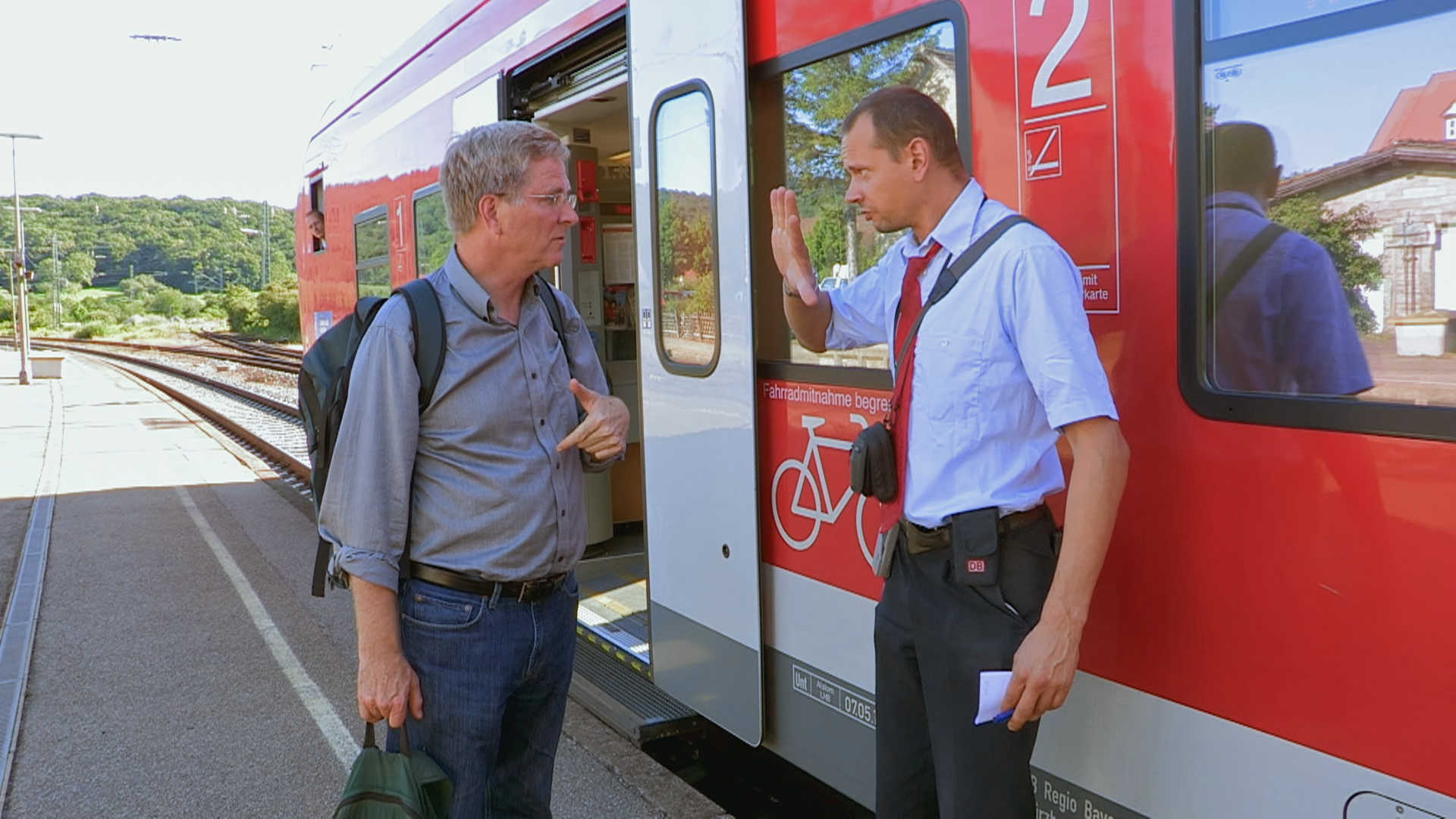 Rick Steves speaks with a train conductor