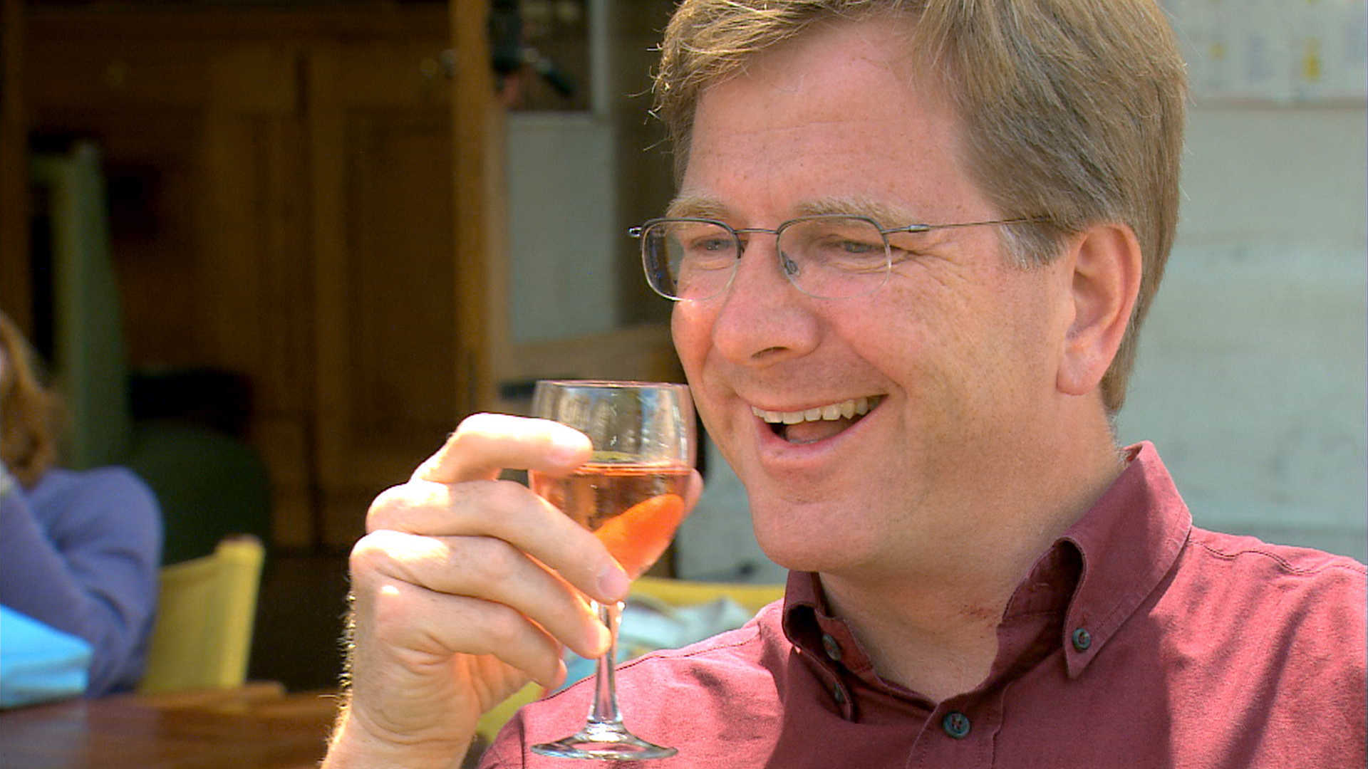 Rick Steves drinks a rose