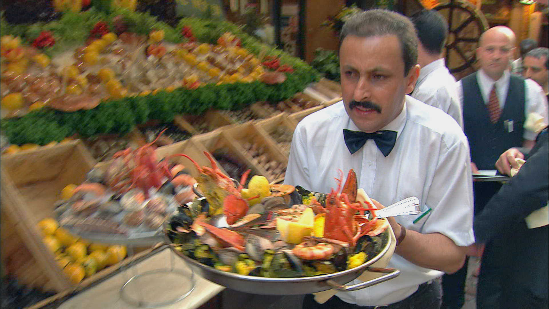 A waiter moves quickly with a plate of hot seafood