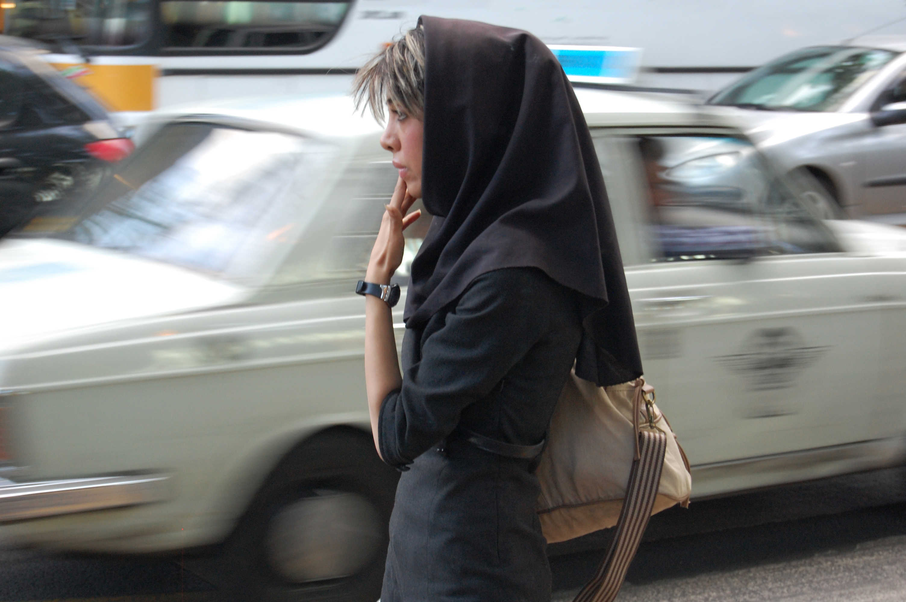 Iranian woman with traffic whizzing by.