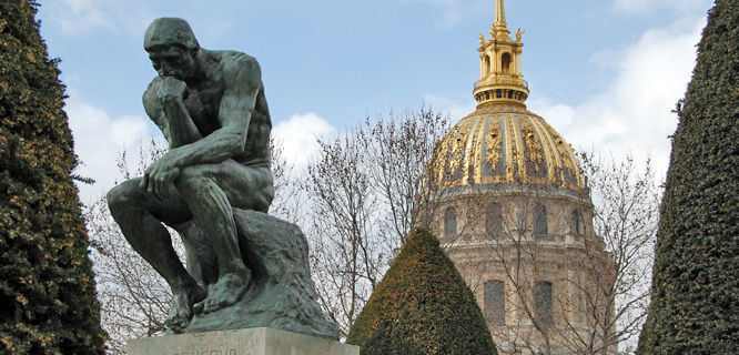 The Thinker by Auguste Rodin with dome of Hôtel des Invalides, Rodin Museum Gardens, Paris, France