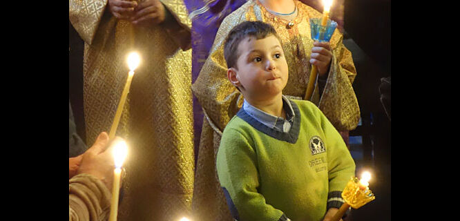 Child at Easter service, Nafplio, Greece