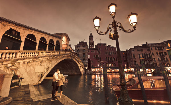 Kissing couple and Rialto Bridge, Venice, Italy