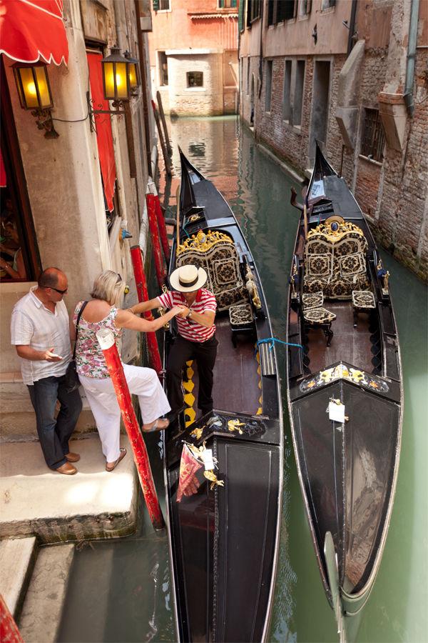 Tourist boarding a gondola, Venice, Italy