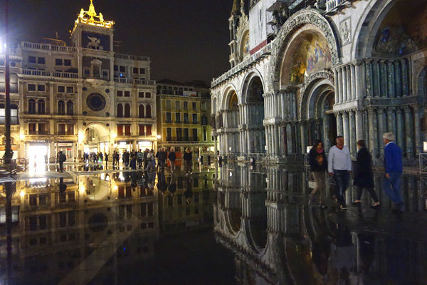 St. Mark's Square during acqua alta (flood) with Clock Tower and St. Mark's Basilica, Venice, Italy