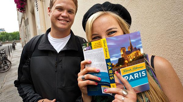 A woman smiling behind a Rick Steves Paris guidebook
