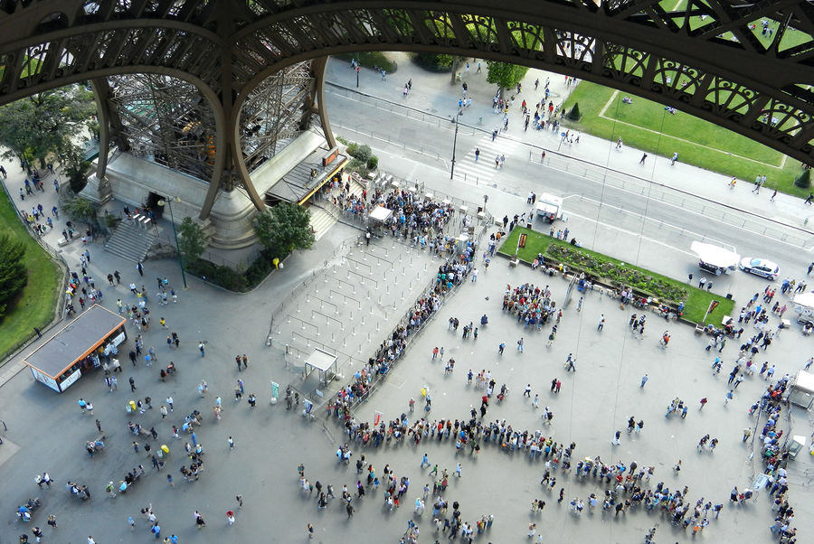 Ticket buyers waiting in line under the Eiffel Tower, Paris, France