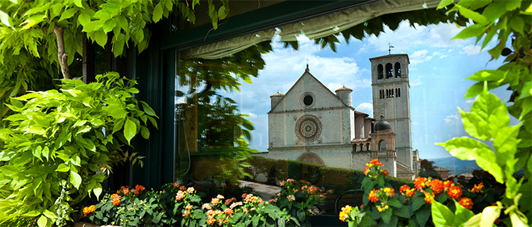 Basilica of St. Francis as reflected in nearby window, Assisi, Italy