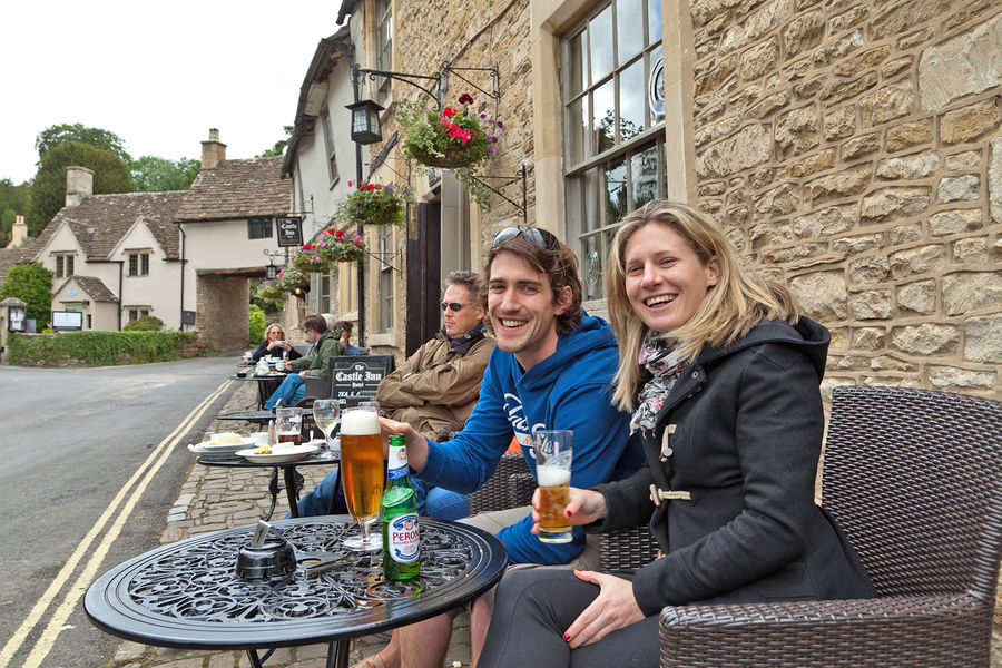 A couple drinking at a pub in the Cotswolds, England