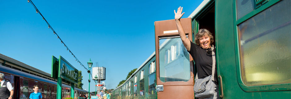 A woman waving from aboard a train, Swanage, England