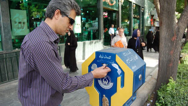 Man making a donation to a religious offering box, Iran