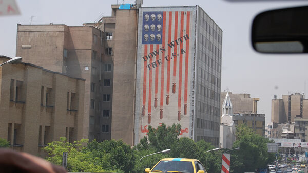 """A mural of an sideways American flag on the side of a building that says """"Down with the USA"""", Iran"""