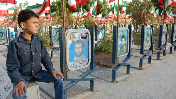 A boy sitting near the graves, Iran