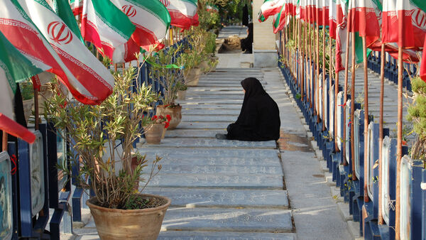 A mother rests near graves, Iran