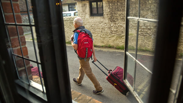 A man rolling his luggage in Alfriston, England