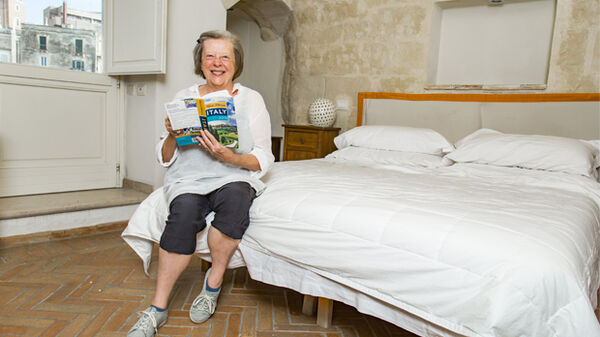 A woman sitting on her hotel bed, Matera, Italy