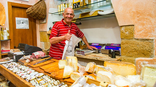 A smiling cheesemonger in Pienza, Italy