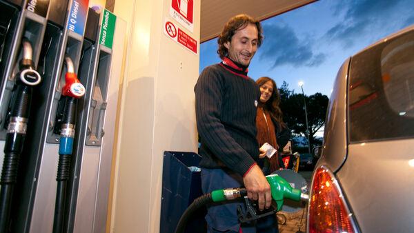 Man using pump at gas station