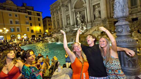 People throwing coins in the Trevi Fountain, Rome, Italy