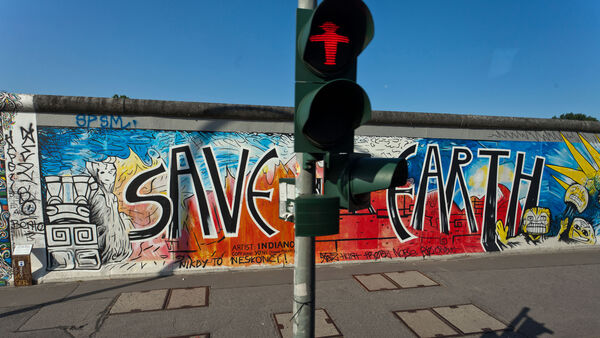 Ampelmann signal in front of wall mural, Berlin, Germany