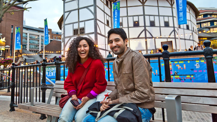 Couple in front of Shakespeare's Globe Theatre, London, England