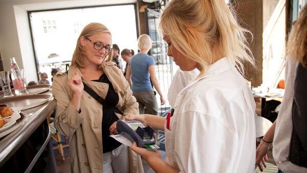 Waitress taking payment in restaurant in Copenhagen, Denmark