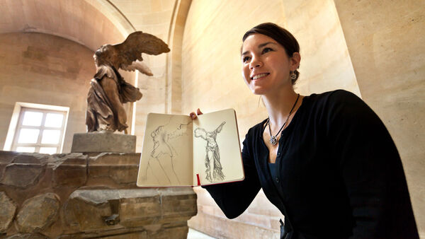 Girl holding sketchbook in front of Winged Victory of Samothrace, Louvre Museum, Paris, France