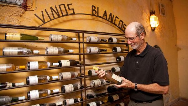 Man holding wine bottle in wine cellar, Toledo, Spain