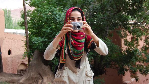 Woman using camera, Iran