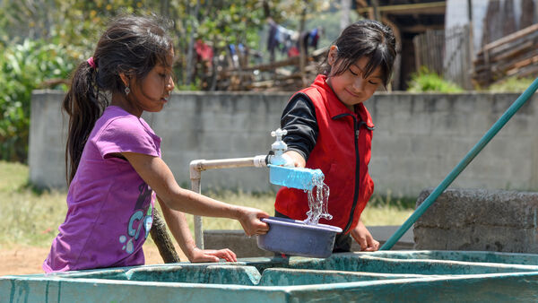 Girls pouring water from a tap, Guatemala