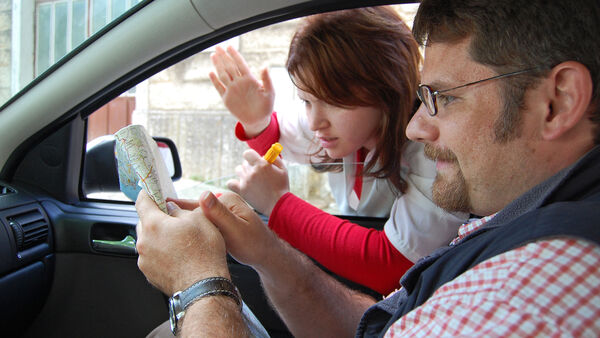 Man in car and woman looking at a map
