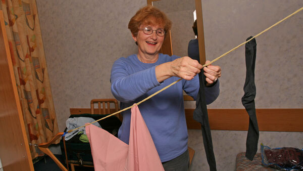 Woman hanging up laundry on a clothesline in hotel room
