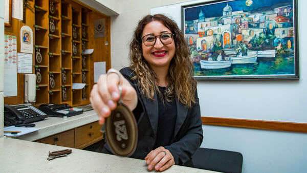 Woman holding keys at hotel reception desk