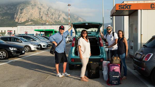People in rental car station parking lot, France