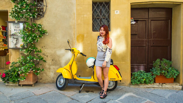 Vespa parked with driver, Pienza, Italy