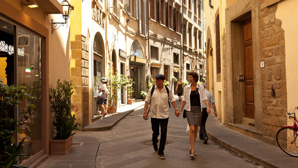 Couple walking on side street, Florence, Italy
