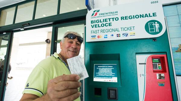 Man buying rail ticket at self-service machine, Sicily