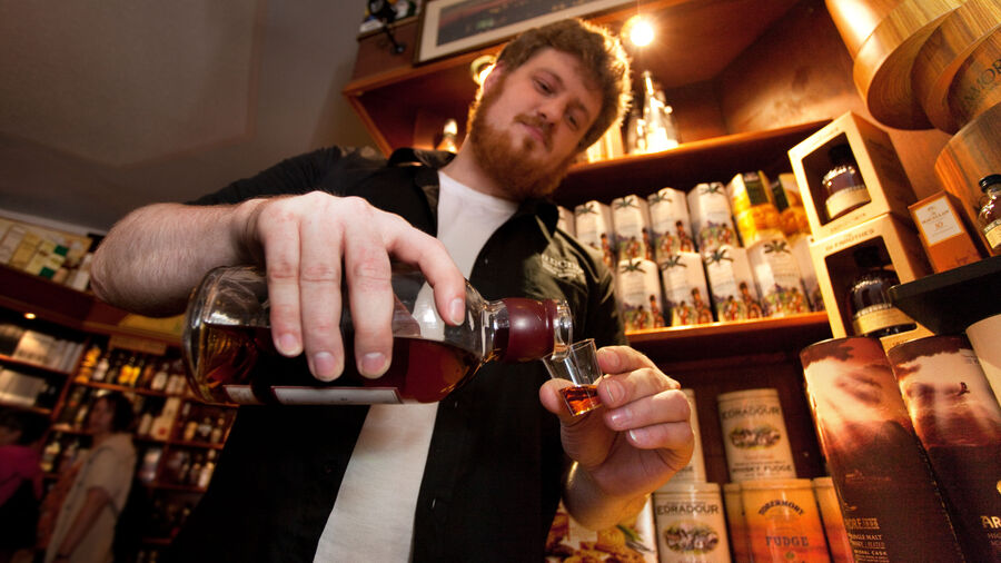 Bartender pouring whisky shot, Inverness, Scotland