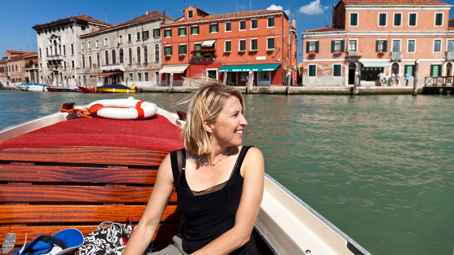 Woman on water taxi ride to Murano, Venetian lagoon, Italy