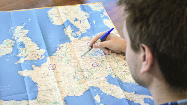 Person marking a map with a pen