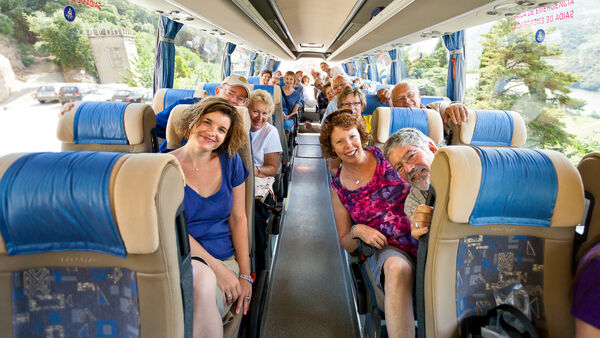 Happy travelers on tour bus