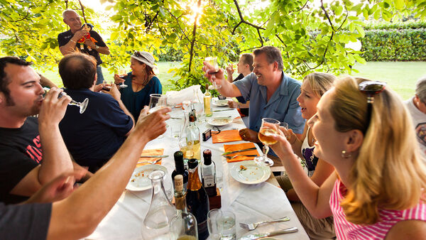 People having dinner outdoors in Tuscany