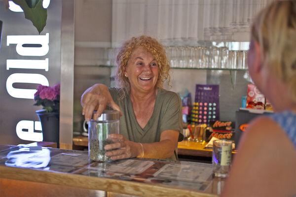 "Budtender proffering marijuana at a ""coffeeshop"" in Amsterdam"