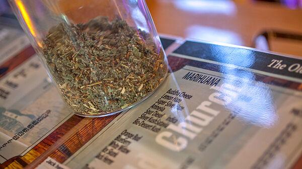 """Jar of marijuana atop a """"coffeeshop"""" counter"""