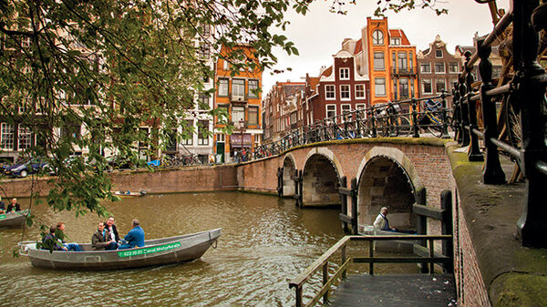 Pleasure boats floating toward the arches of a canal bridge in Amsterdam